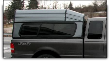 Ranger aluminum truck cap with drop front roof style and glass/awning/glass side windows.